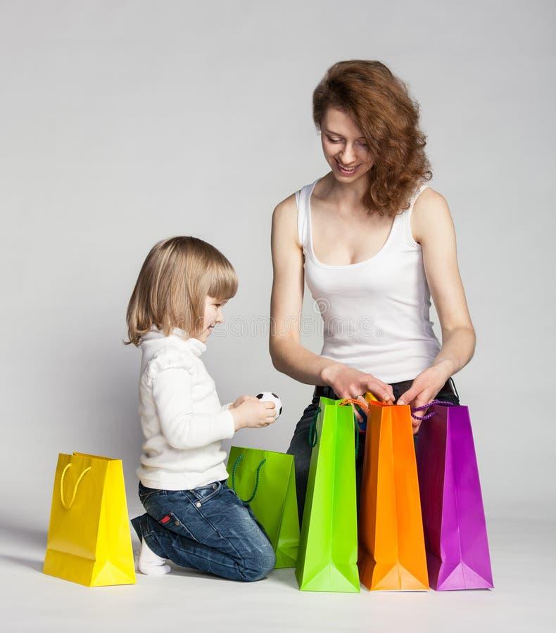 Menina com sua mãe que olha sacos de compras internos foto de stock royalty free