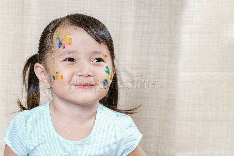 Menina com a sujeira colorida pintada em sua cara crianças que sorriem e que apreciam o conceito do desenvolvimento fotos de stock royalty free
