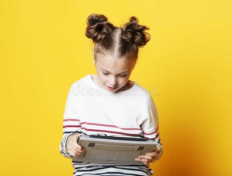 Menina com a tabuleta no fundo amarelo do estúdio imagens de stock