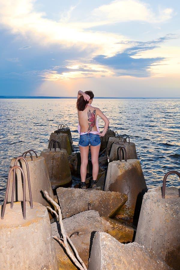 A menina com tatuagem da borboleta suporta sobre da costa do golfo com estruturas concretas foto de stock