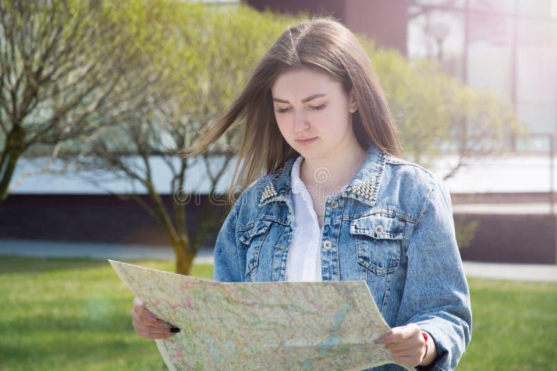 Menina com telefone e mapa está procurando a estrada Garota turista bonitinha com roupas de jeans andando pela rua no verão. imagens de stock royalty free