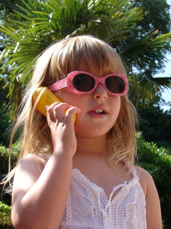 Menina com telemóvel das crianças imagem de stock