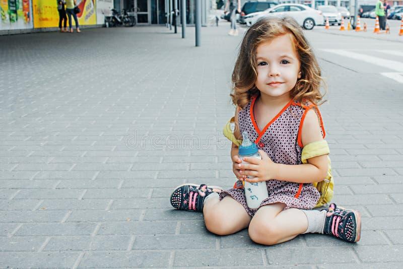 A menina com trouxa e a garrafa de bebê viajam no aeroporto ou a estação de trem, crianças viaja fotos de stock royalty free