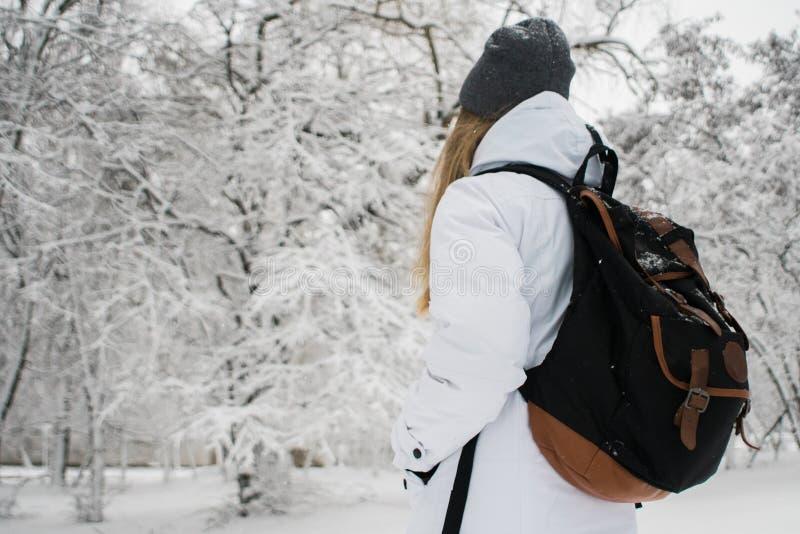 Menina com trouxa que anda na neve nas montanhas e no alpinismo durante os feriados de inverno fotos de stock