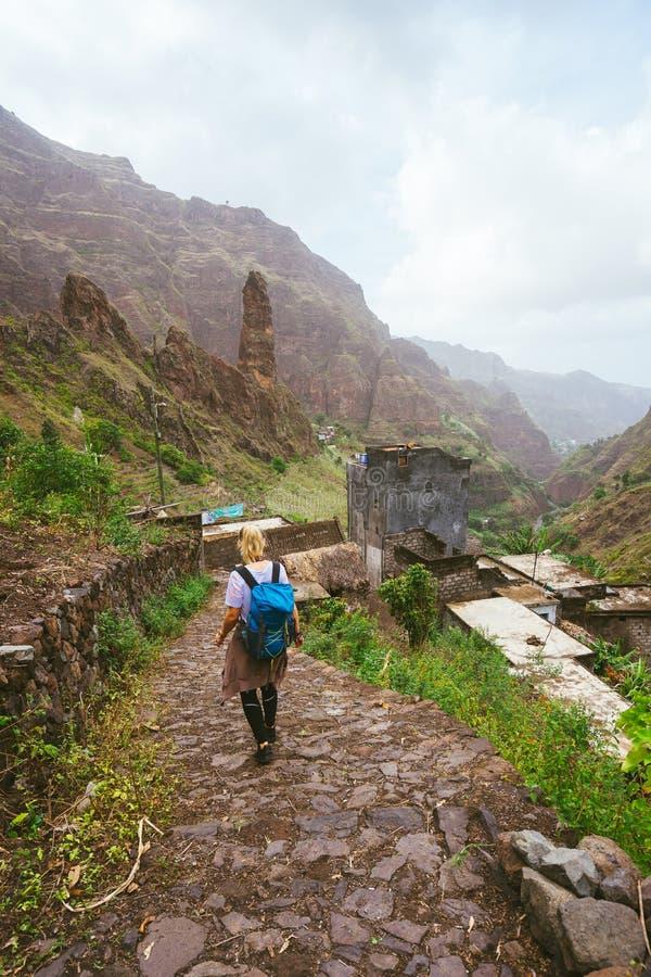 Menina com trouxa que anda para baixo ao longo da rota trekking ao vale verdejante de Xo-Xo Os picos de montanha e a vila local s imagem de stock royalty free