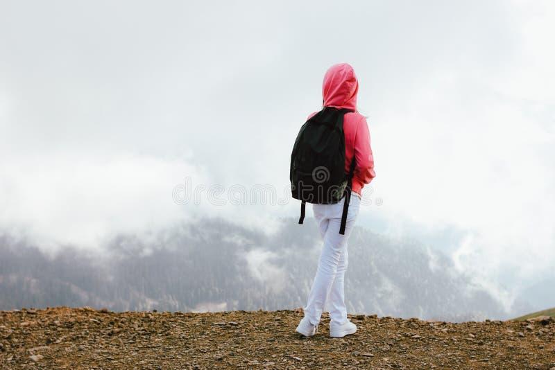 Menina com a trouxa que olha em montanhas bonitas nas nuvens, conceito do Tween do curso da família foto de stock royalty free