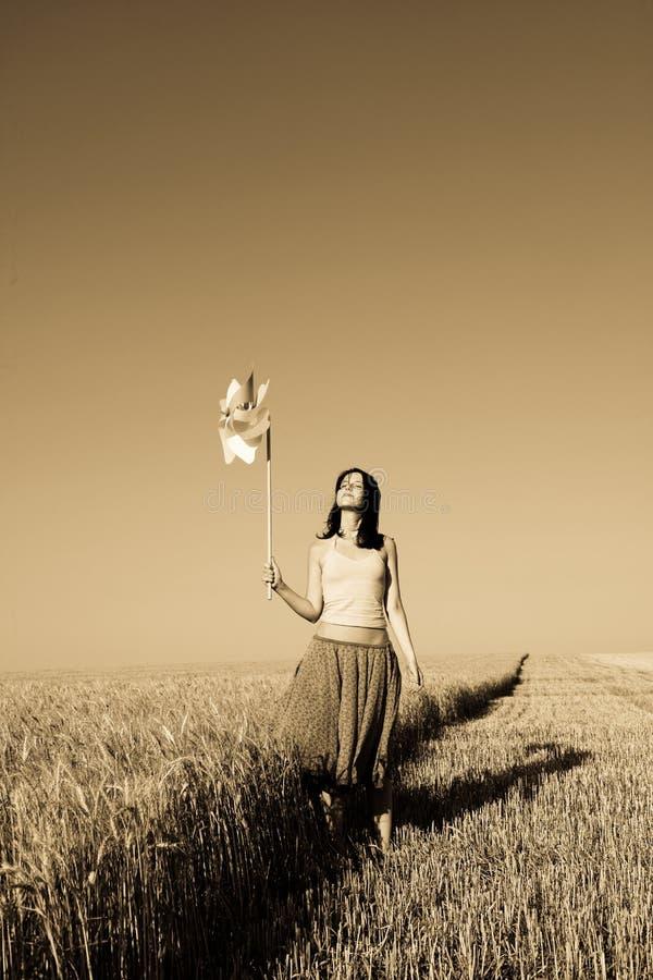Menina com a turbina de vento no campo de trigo imagem de stock