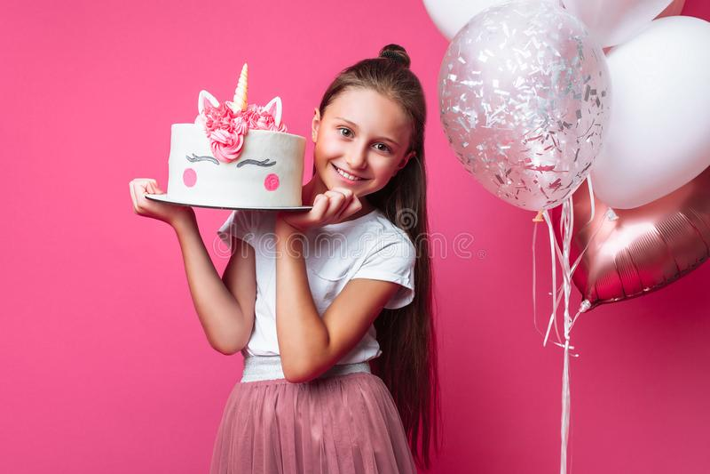 Menina com um bolo para um aniversário, no estúdio em um fundo cor-de-rosa, humor festivo, close-up, bolo do desenhista imagens de stock royalty free