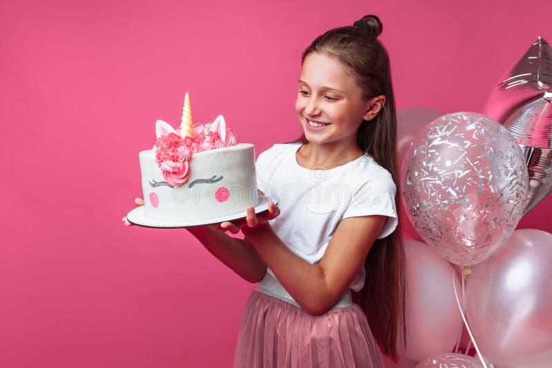 Menina com um bolo para um aniversário, no estúdio em um fundo cor-de-rosa, humor festivo, close-up, bolo do desenhista foto de stock
