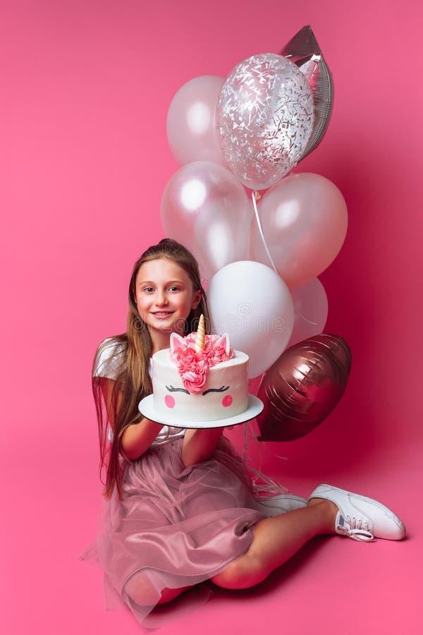 Menina com um bolo para um aniversário, no estúdio em um fundo cor-de-rosa, humor festivo, no crescimento completo, nas mãos de u imagens de stock royalty free