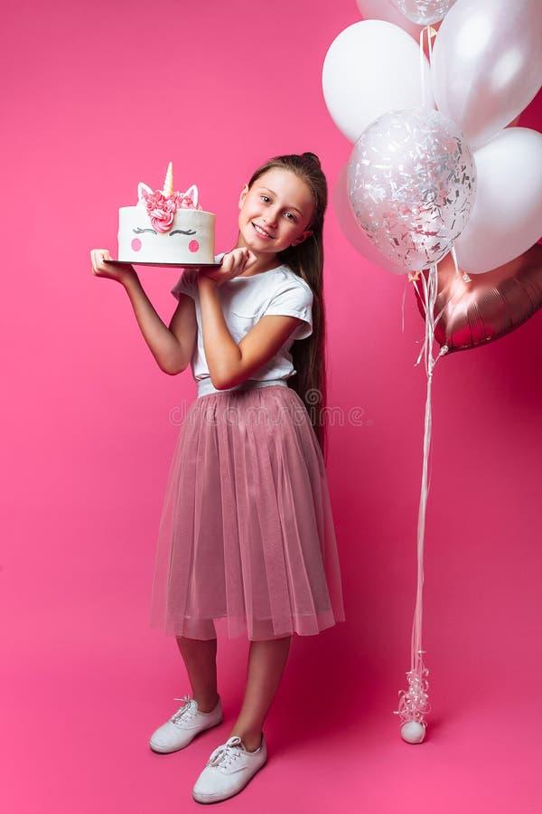 Menina com um bolo para um aniversário, no estúdio em um fundo cor-de-rosa, humor festivo, no crescimento completo, nas mãos de u fotos de stock