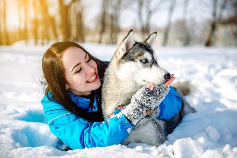 Menina com um cão no cão de puxar trenós do inverno foto de stock