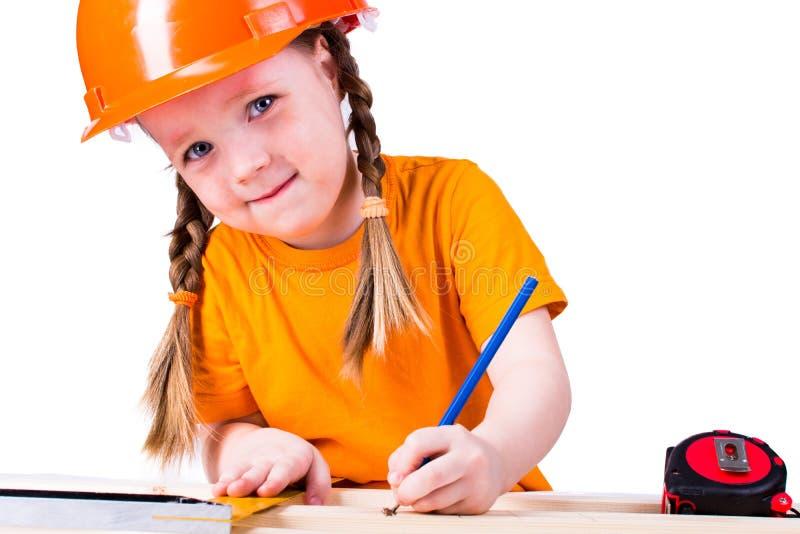 Menina com um capacete da construção foto de stock royalty free