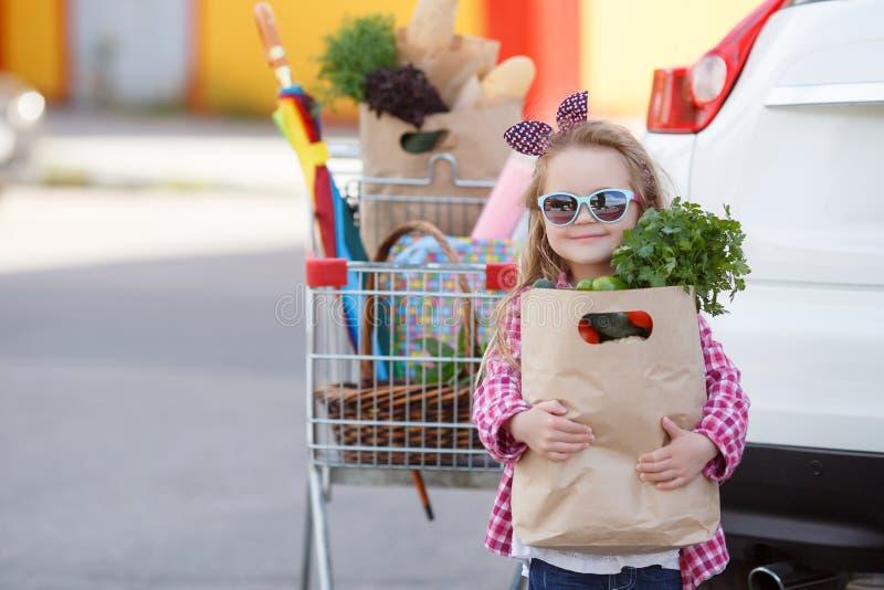 Menina com um carrinho de compras completo dos mantimentos perto do carro fotografia de stock