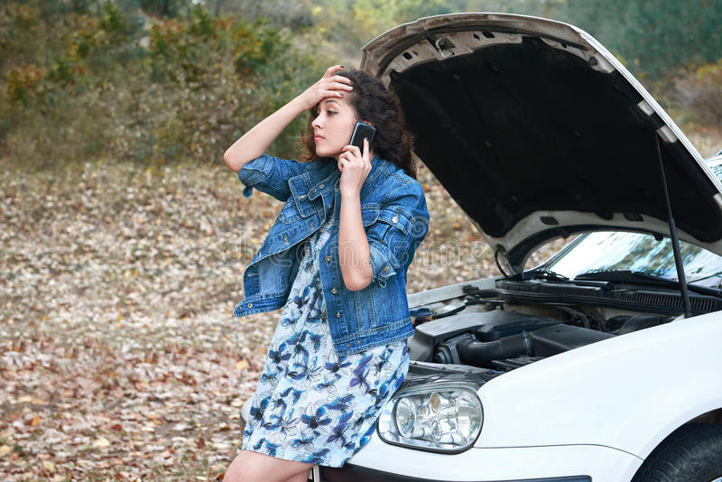 A menina com um carro quebrado, abre a capa, chamada para a ajuda fotos de stock royalty free