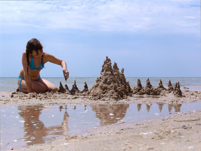 Menina com um castelo da areia foto de stock