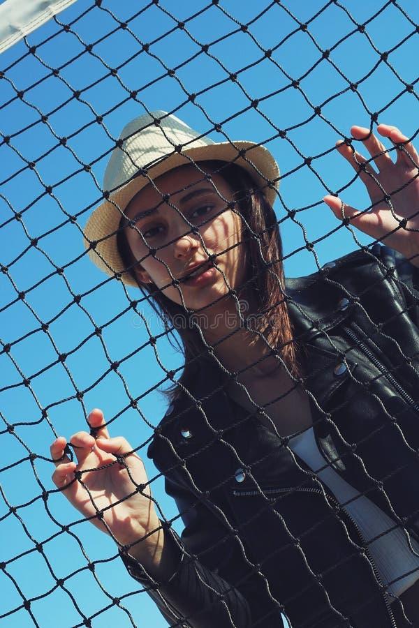 Menina com um chapéu atrás de uma rede imagens de stock royalty free