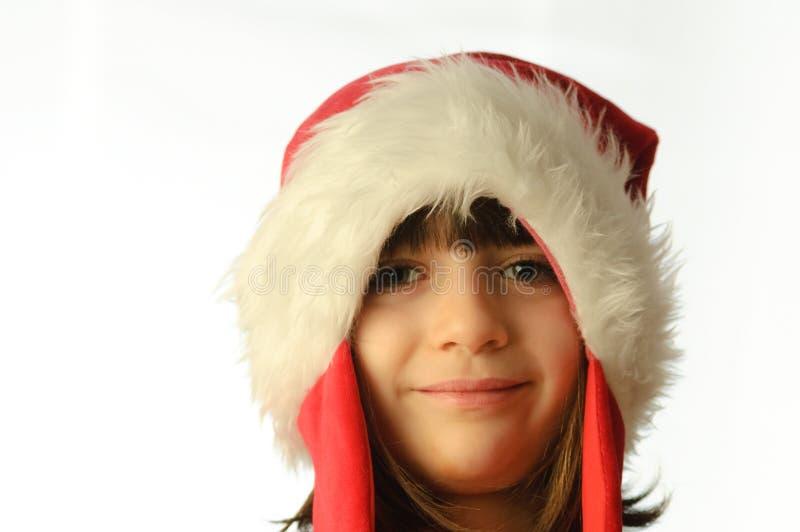 Menina com um chapéu de Papai Noel puxado para baixo fotografia de stock royalty free