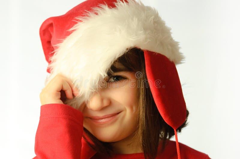 Menina com um chapéu de Papai Noel puxado para baixo fotos de stock