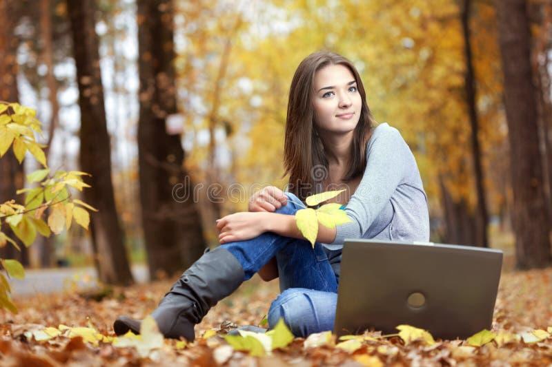 Menina com um computador em um parque do outono que aprecia o Internet imagens de stock royalty free