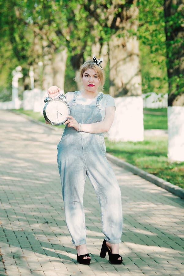 Menina com um despertador do pulso de disparo em suas mãos Gestão de tempo T fotografia de stock