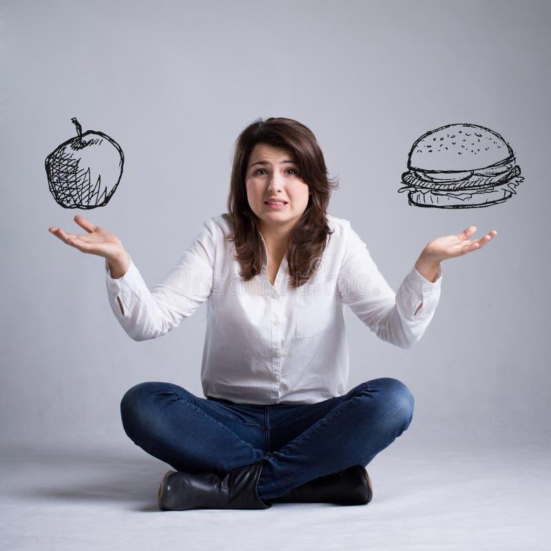 Menina com um dilema sobre o alimento fotografia de stock