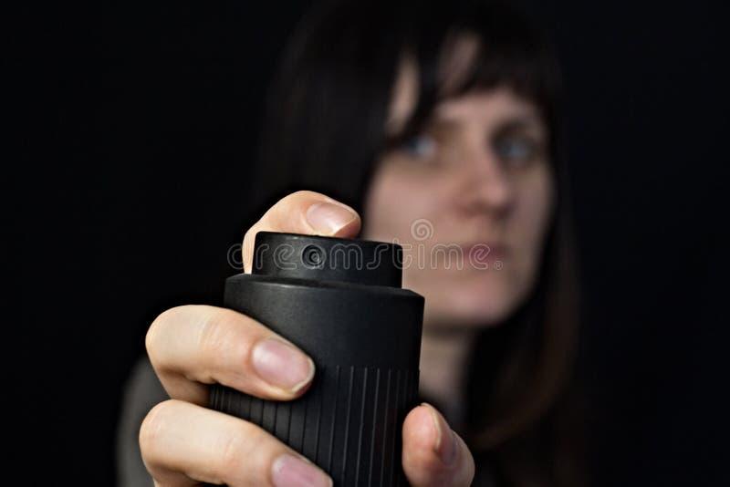 Menina com um g?s, spray de pimenta, close-up, fundo preto imagens de stock royalty free