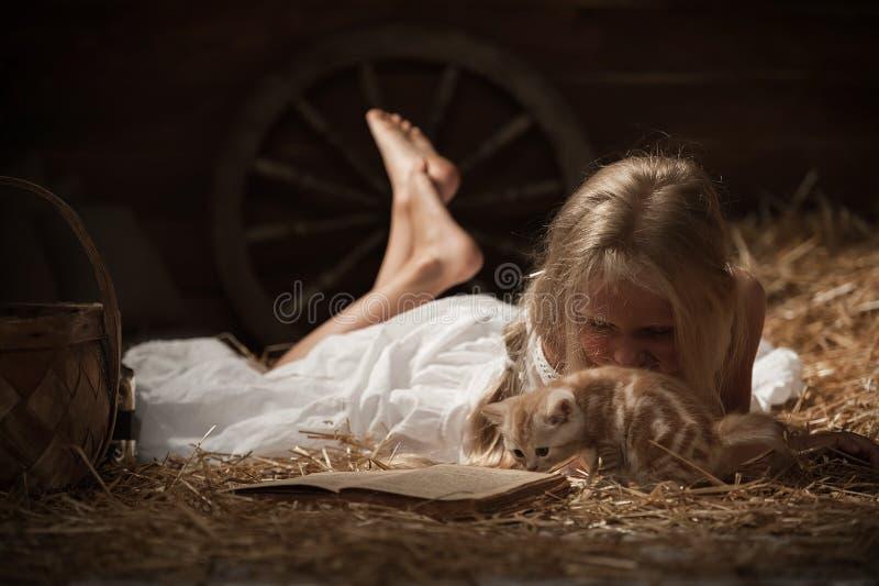 Menina com um gatinho no feno imagem de stock royalty free