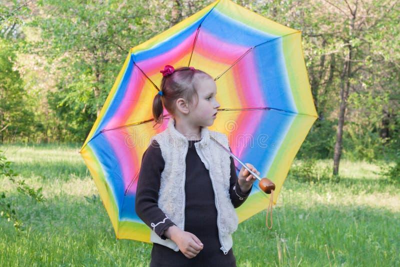 A menina com um guarda-chuva multi-colorido foto de stock
