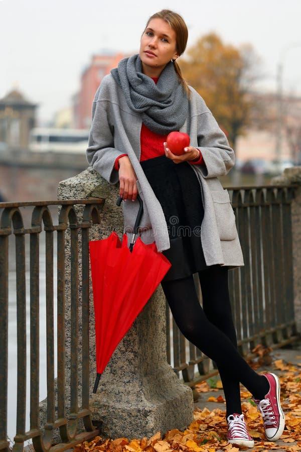 Menina com um guarda-chuva vermelho e um Apple em uma caminhada foto de stock royalty free