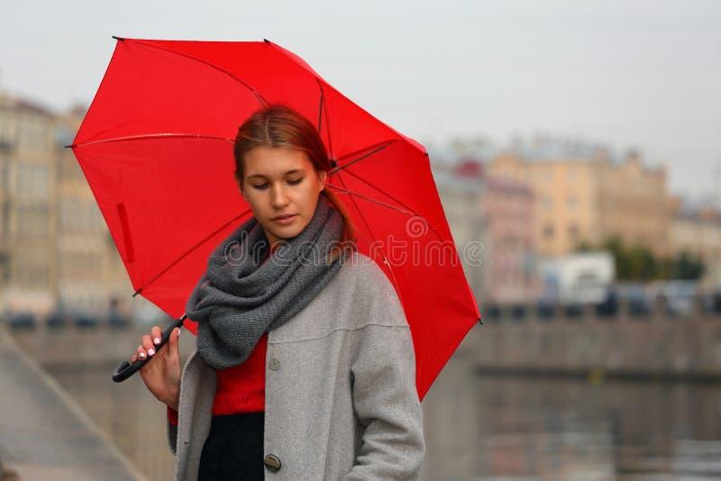 Menina com um guarda-chuva vermelho no fundo do canal da cidade foto de stock royalty free