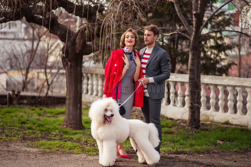 Menina com um homem e uma caniche branca imagens de stock royalty free
