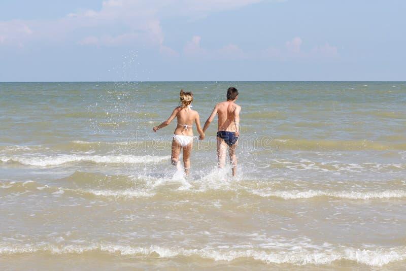 Menina com um indivíduo que funciona no mar foto de stock royalty free