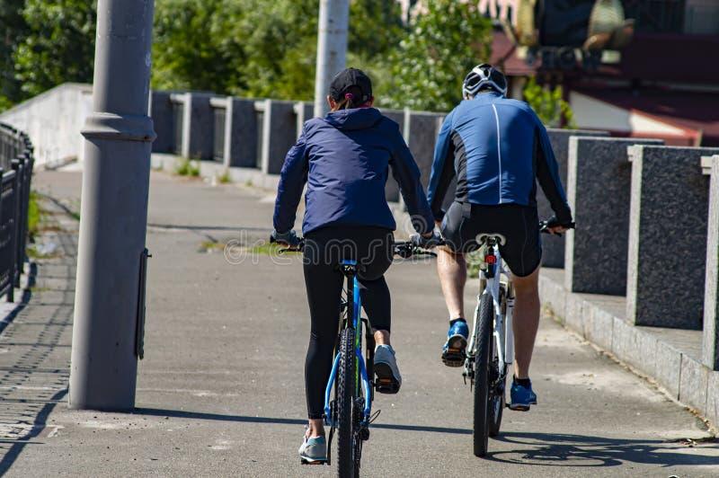 Menina com um indivíduo que monta uma bicicleta Vista traseira Esportes e recrea??o foto de stock royalty free