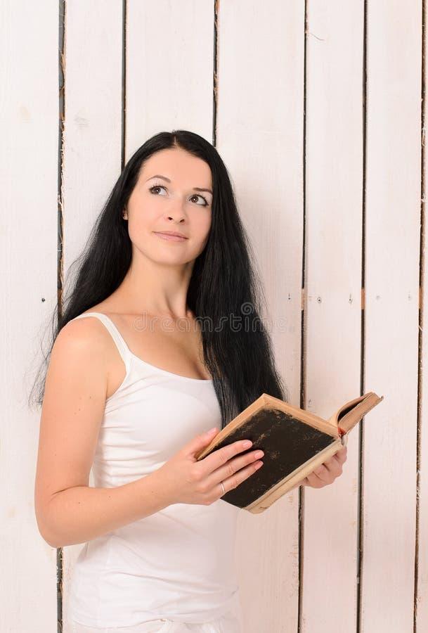 Menina com um livro que olha acima fotos de stock