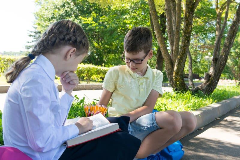 Menina com um menino que faz trabalhos de casa após a escola, fora, lendo um livro e tomando notas fotografia de stock