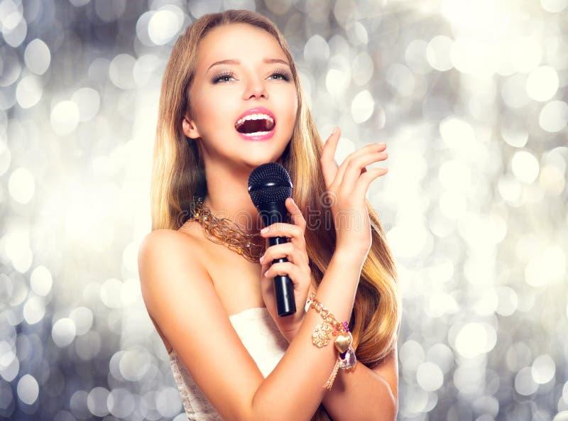 Menina com um microfone que canta fotos de stock royalty free