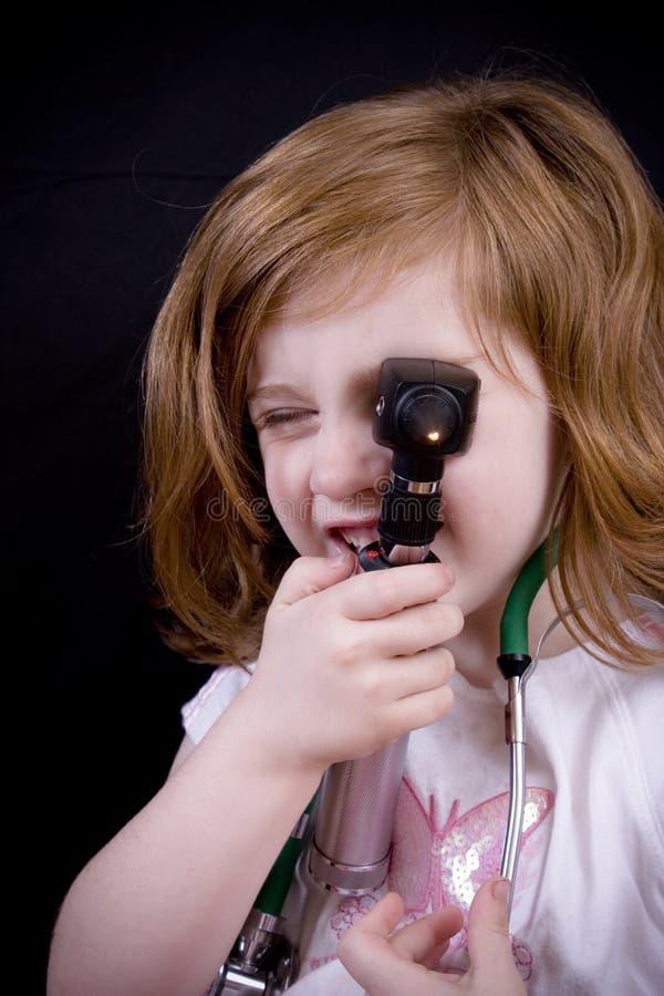 Menina com um otoscope fotos de stock