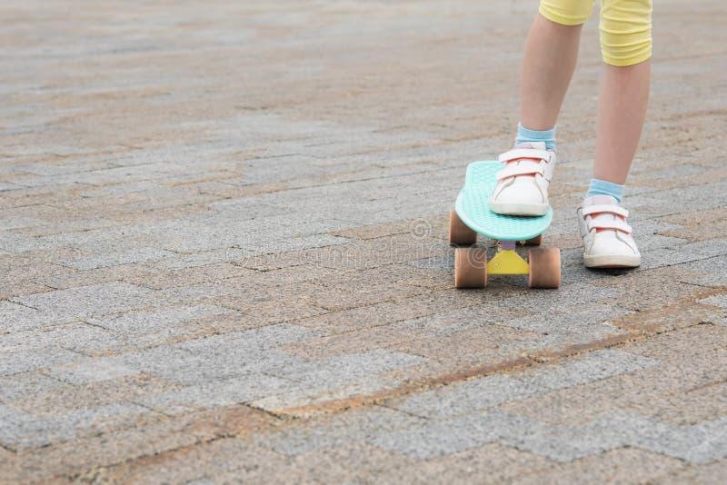 a menina com um pé está na terra e na outro com um pé em um skate contra um fundo do asfalto fotografia de stock royalty free