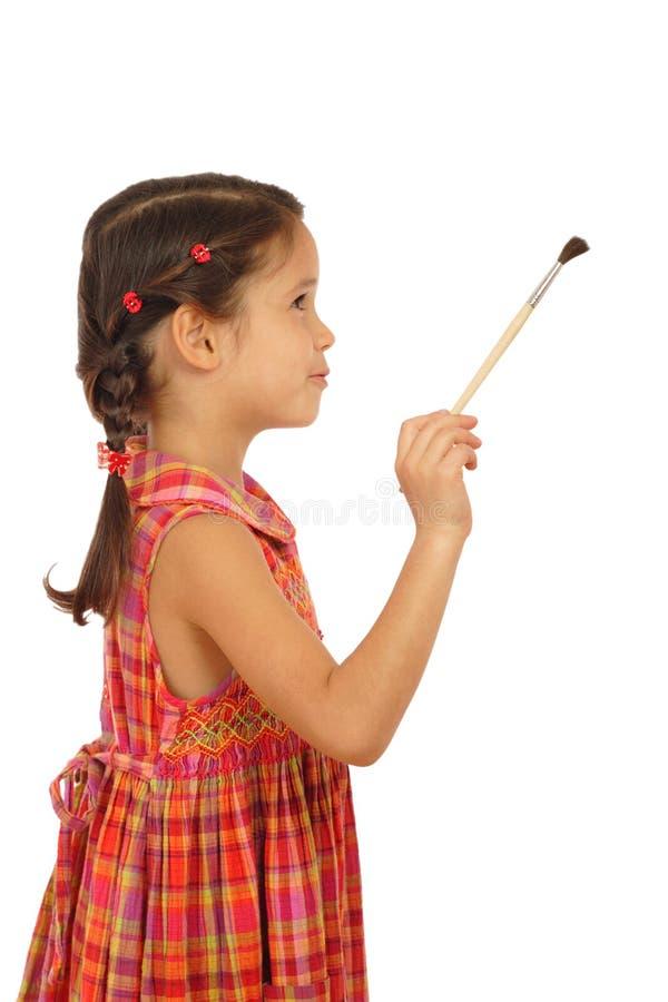 Menina com um pincel, vista lateral fotografia de stock