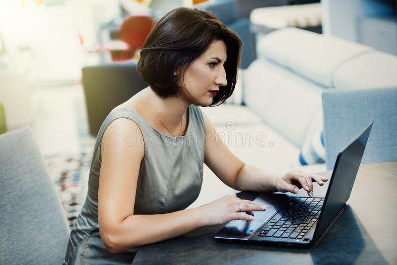 Menina com um portátil na tabela fotografia de stock