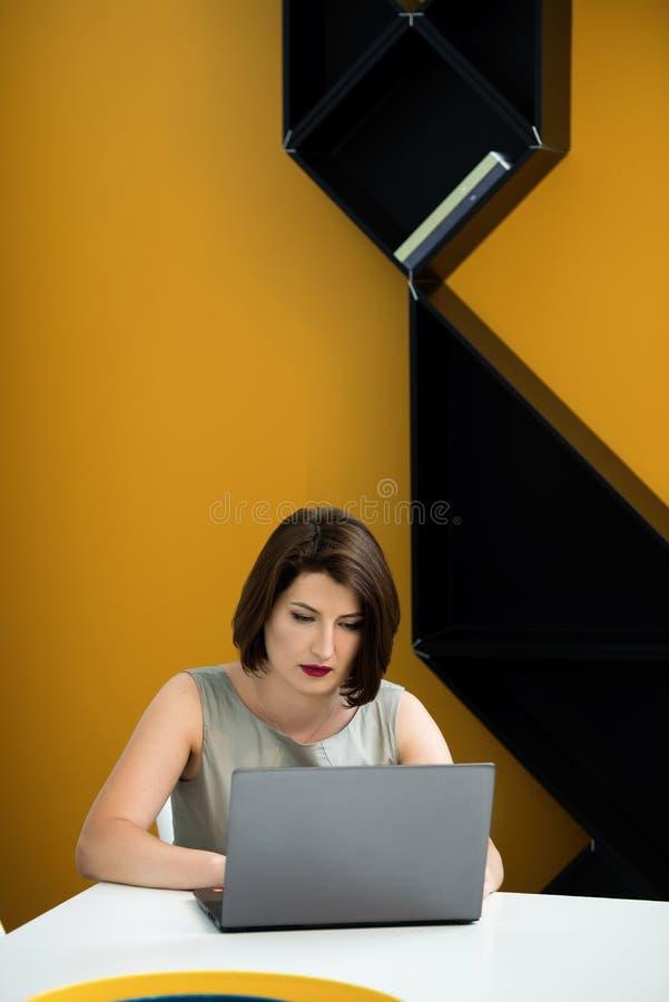 Menina com um portátil na tabela imagem de stock royalty free