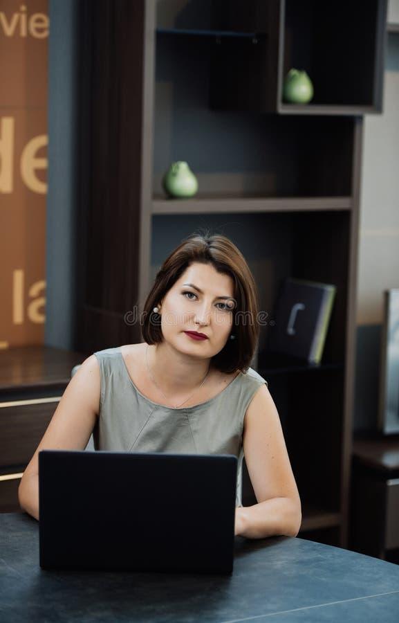 Menina com um portátil na tabela foto de stock royalty free