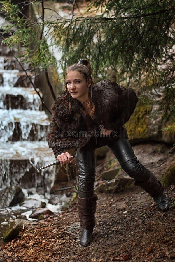 Menina com um punhal com um punhal perto de uma cachoeira fotografia de stock royalty free