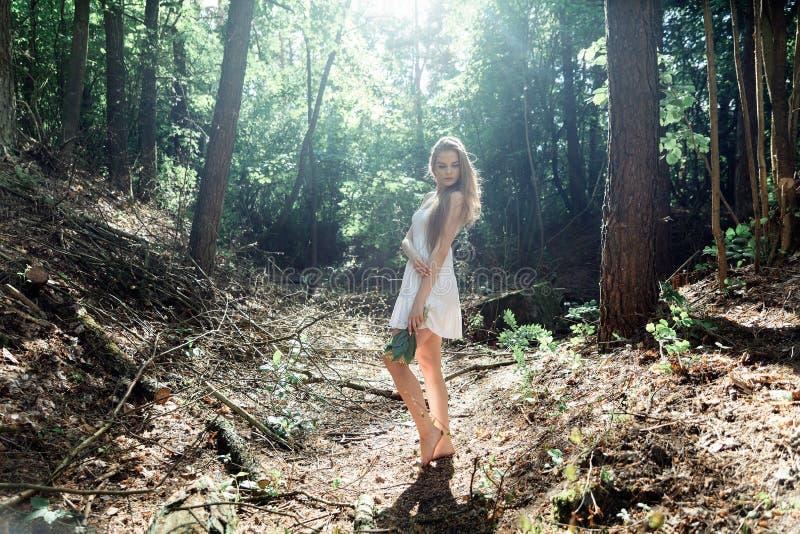 Menina com um ramalhete das flores e de um vestido branco em uma floresta ensolarada imagens de stock royalty free