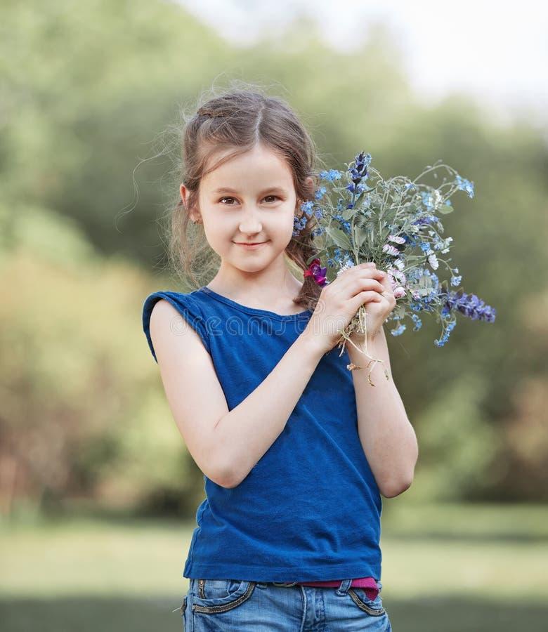 Menina com um ramalhete de flores selvagens fotografia de stock royalty free