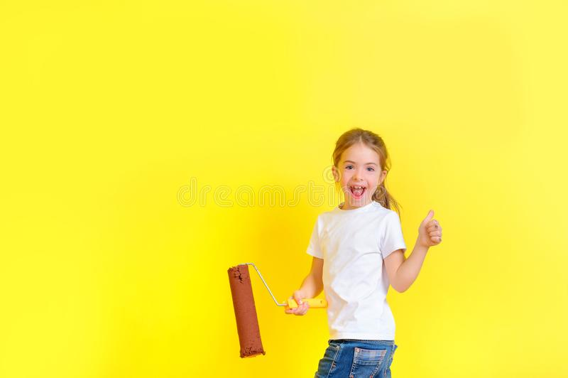 A menina com um rolo para pintar em suas mãos está jogando o tolo ao redor a parede pintada imagens de stock royalty free