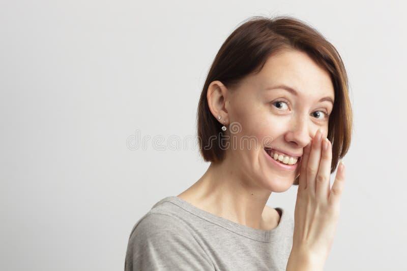A menina com um sorriso compartilha do segredo fotos de stock