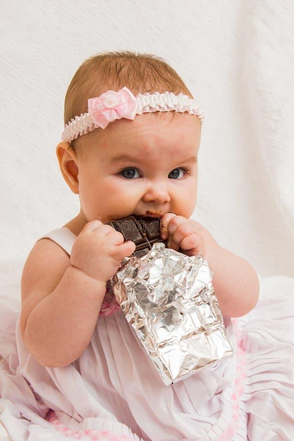 Menina com uma barra de chocolate fotos de stock royalty free