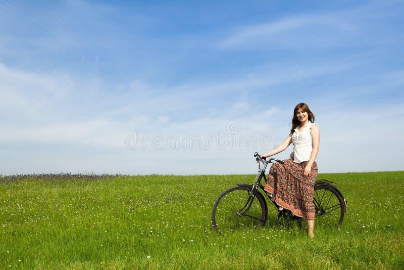 Menina com uma bicicleta imagem de stock
